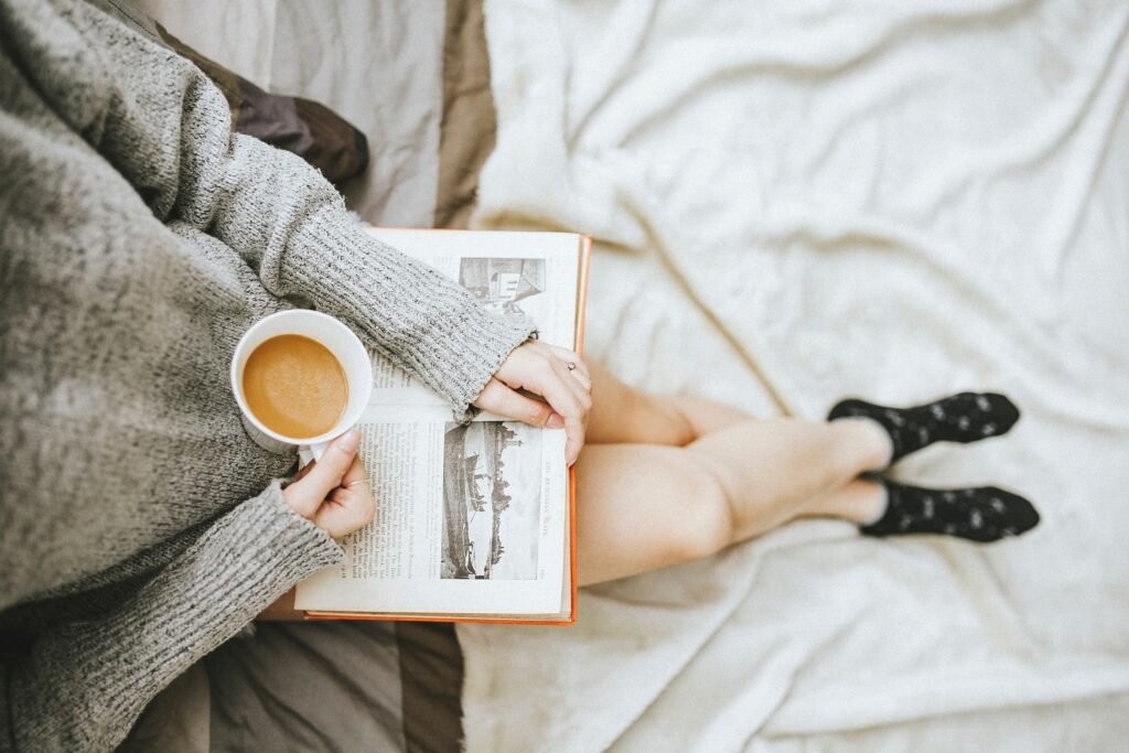 woman sitting holding a cup of coffee and reading book