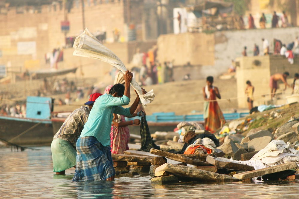 women beating laundry in river